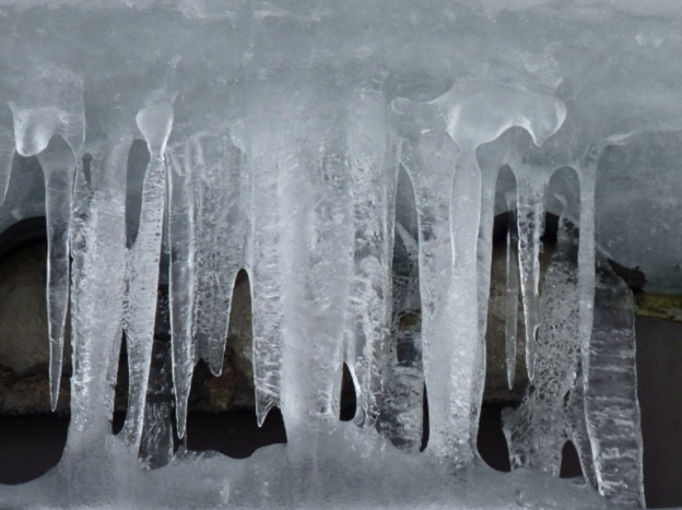 frozen icicles hanging from an air conditioner freezing from blocked usage