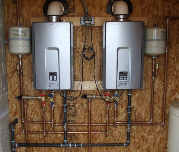 a pair of tankless water heaters installed in the back of a wooden plywood baseboard in a home basement by air leaders inc